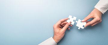 Deux personnes assemblent des pièces de puzzle