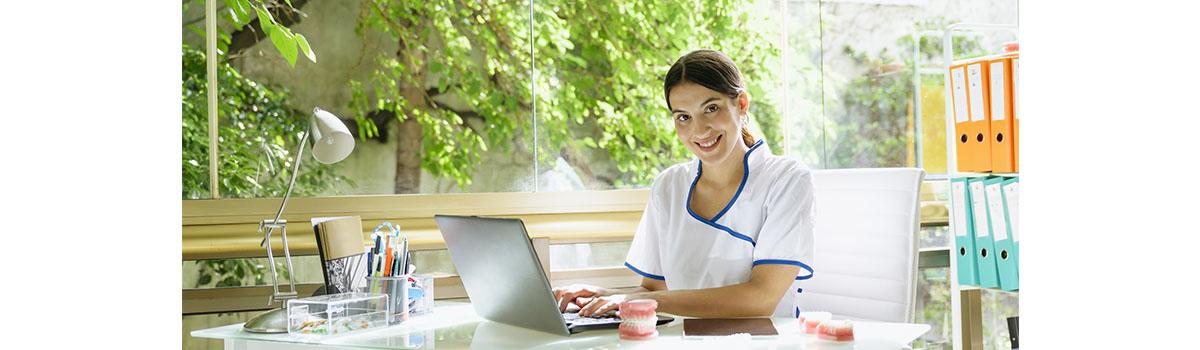 Une infirmière libérale assise à son bureau