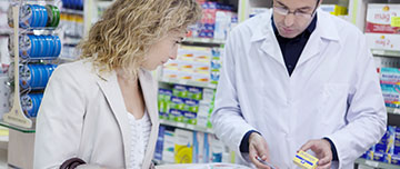 Un pharmacien renseigne une cliente sur la posologie d'un médicament