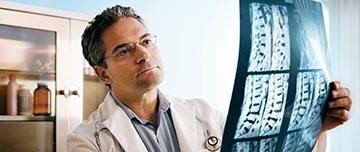 Un médecin observe une radio du rachis