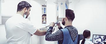 Un dentiste installe son patient pour une radio panoramique