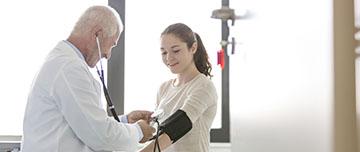 Un homme médecin ausculte une adolescente