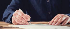 Un homme rédige un contrat.