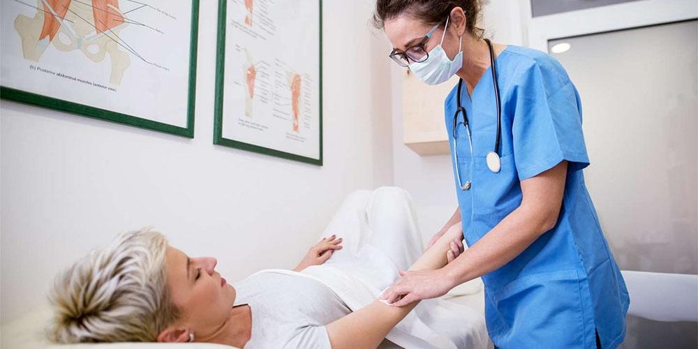 Une infirmière exerce un acte de soin sur son patient.