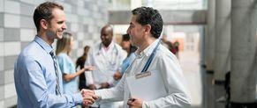 Un professionnel de santé serre la main d'un homme d'affaire.